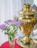 Forntida apparat för att göra te och vasen av blommor vid fönstret arkivfoton