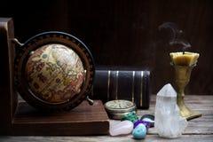 Forntida astrologi Gamla astrologijordklot och böcker med stearinljuset arkivbild