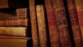 Forntida böcker i en bokhylla lager videofilmer