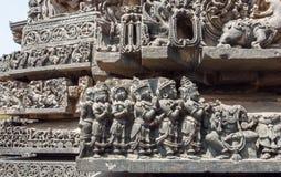 Forntida be folk på den gamla väggen av den hinduiska templet Carvings för Sculpured stenlättnad från den 12th århundradetemplet, Arkivfoto