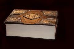 Forntida bok i det lyxiga bandet som isoleras på svart bakgrund Arkivfoton
