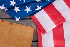 Forntida bok och USA flagga Arkivbild