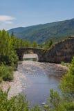 Forntida bro över bergfloden Arkivfoton