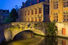 Forntida bro på den Dijver kanalen i Bruges på natten (Belgien) Royaltyfria Bilder