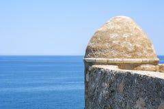 Forntida brun stenvägg nära det blåa havet och den blåa himlen Royaltyfri Fotografi