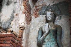 Forntida Buddhastaty bredvid väggen Arkivbild