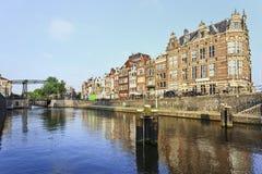 Forntida byggnader och en kanal i Amsterdam den historiska mitten på gryningen, Nederländerna Royaltyfri Foto