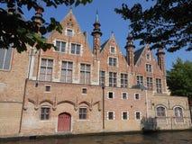 Forntida byggnader på en kanal i härliga Brugge arkivfoto