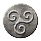 Forntida celtic triskelesymbol i sten Arkivfoton