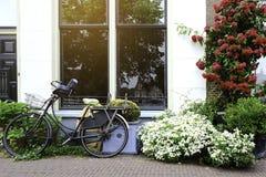 Forntida cyklar parkerade framme av huset Cykel som lutar på de stora fönstren på vägrenen royaltyfria bilder