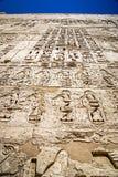 Forntida egyptisk hieroglyfer som snidas på tempelväggar arkivbild