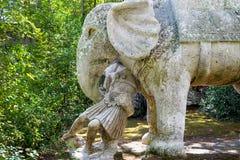 Forntida elefant och Roman Soldier för renässansskulpturkrig i den berömda Parco deien Mostri som kallas också Sacro Bosco eller  royaltyfri fotografi