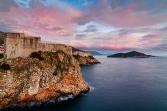 Forntida fästning på klippkanten av Dubrovnik på solnedgången med rosa moln royaltyfria bilder