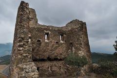 Forntida förstörd fästning Allvarlig emoticon på stenväggen royaltyfria bilder