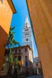 Forntida gata i Modena med en sikt av det vita tornet på bakgrund för blå himmel Royaltyfria Foton