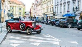 Forntida gator av den europeiska staden av Prague Antika byggnader och retro bilar Fotografering för Bildbyråer