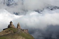 Forntida Gergeti Treenighetkyrka som är hög i de Kaukasus bergen, Georgia royaltyfri foto