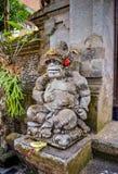 Forntida gudstatyer för konst med leende på Bali Royaltyfri Bild