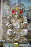 Forntida gudstatyer med leende på Bali Royaltyfri Foto