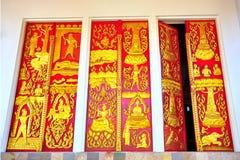 Forntida guld- snida trädörr av det thailändska tempelet Royaltyfria Foton