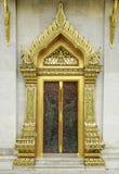Forntida guld- snida trädörr av det thailändska tempelet Royaltyfria Bilder