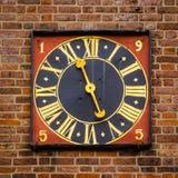 Forntida guld- tornklocka på en röd brickwalll Arkivfoto