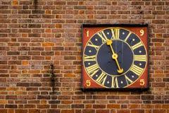 Forntida guld- tornklocka på en röd brickwalll Fotografering för Bildbyråer