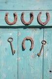 Forntida hästsko och rostig tangent på trägammal dörr Arkivbild