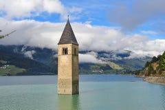 Forntida halva-doppat klockatorn i Graun im Vinschgau royaltyfri foto