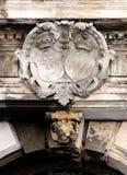 Forntida heraldisk vapensköld som är skadad Fotografering för Bildbyråer