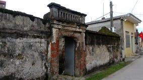 Forntida hus mossed av byvägen arkivfoto
