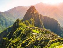 Forntida Inca City av Machu Picchu som är upplyst vid solen Fördärvar av Incan borttappad stad i peruansk djungel Unesco-världsar royaltyfri bild