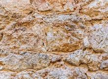 Forntida kärvhetstenvägg Stenhuggeriarbete av sandsten Persikatextur Royaltyfri Bild
