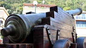 Forntida kanon som riktas till modern byggnad arkivbilder