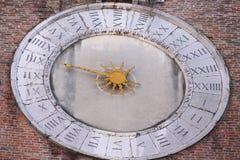 Forntida klocka med en hand som mäter timmarna och den romerska numeren Royaltyfria Bilder