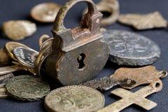 Forntida kopparhängeslott på bakgrunden av mynt och andra antika objekt av det ryska 18th århundradet Arkivfoton