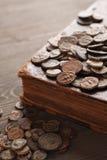 Forntida kopparmynt på den gamla boken Arkivfoto