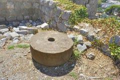 Forntida kvarnsten på jordningen royaltyfria bilder