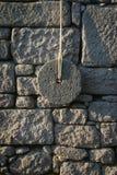 Forntida kvarnsten på väggen royaltyfri fotografi