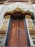 Forntida kyrklig dörr som dekoreras med thailändskt motiv arkivfoton