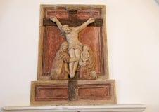 Forntida låg lättnad i stenen av korsfästelsen inom theChurch av San Nicola från Myra, Locorotondo, Italien Arkivbilder