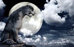 Forntida lejonstaty och ljus måne i natthimlen Arkivbilder