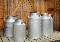 Forntida mjölka cans på mejerilantgård Arkivfoton