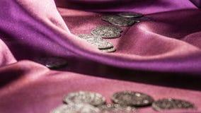 Forntida mynt på purpurfärgad satäng Arkivfoto