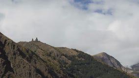 Forntida near montering Kazbek, Kaukasus berg för Gergeti Treenighetkyrka stock video