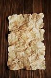 Forntida pergament på träbakgrund Arkivfoto