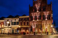 Forntida rad av hus med restauranger under solnedgång i Doesburg arkivbild