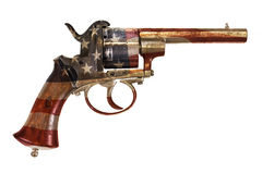 Forntida revolver med amerikanska flaggan som isoleras på vit Royaltyfri Foto