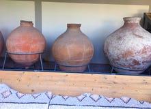 Forntida Roman Amphorae som staplas upp mot en vägg Dessa användes för att bära vin arkivbild