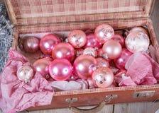 Forntida rosa julgranleksaker i antik resväska arkivbilder